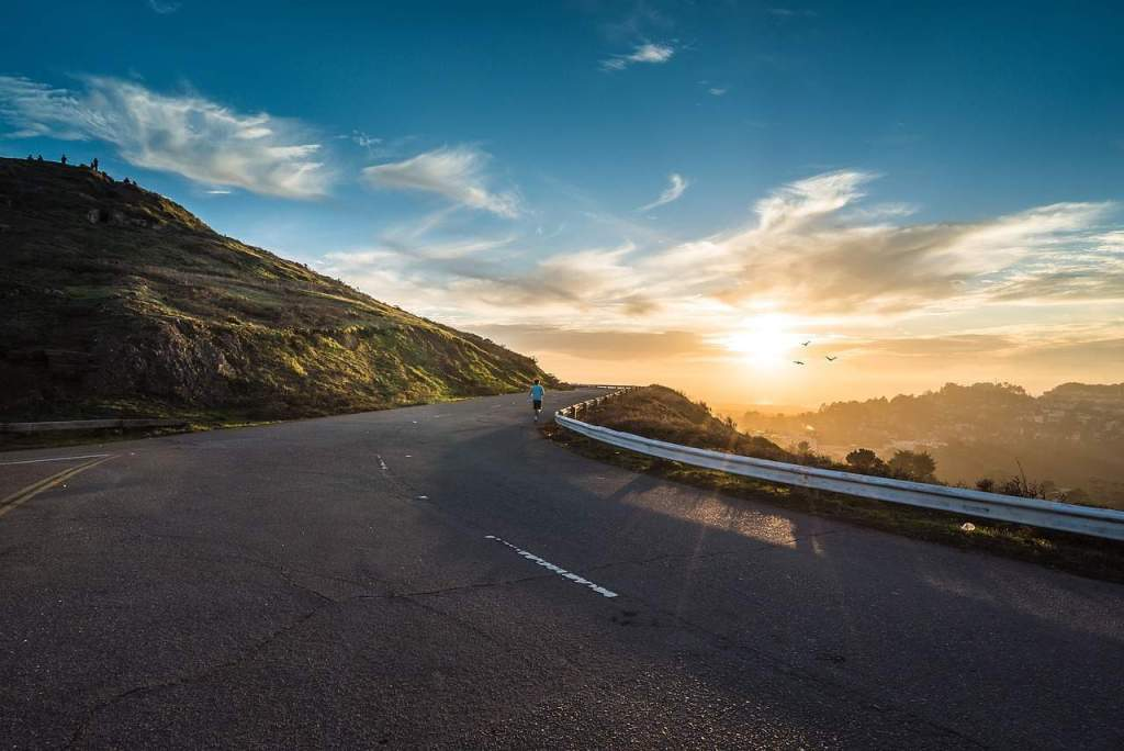 person running on road at sunrise