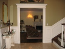 Entrance from foyer to formal living room with white marble fireplace and custom window treatments