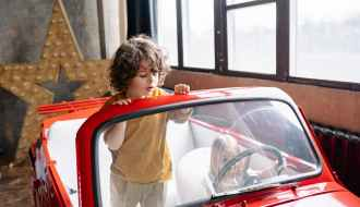 kids playing in car in photo studio