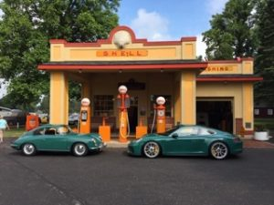 Porsche 356 and GT3 Touring models in front of the iconic Shell Station