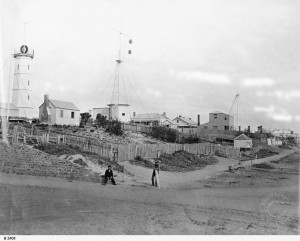 Signal Station, Semaphore. The Pilot is seated at the end of the wall & Signalman William Uden is leaning on the post. In the enclosure is the old wooden room in which the pilots on night duty slept. The two storey house was owned by Richard Jagoe, the shipping reporter. The Time Ball tower on the extreme left was completed by December 1874. The time service commenced on 2nd August, 1875. See research note 545. This view was reproduced in the 'Observer', 27th December, 1924, also on the 21st May, 1904. Photo courtesy of State Library of South Australia B2408.