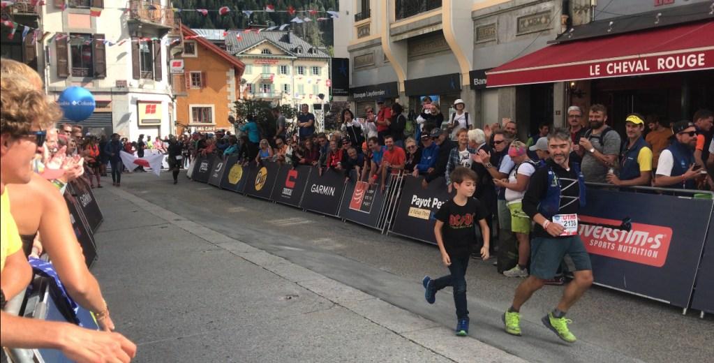a runner and a child finish the 2018 UTMB ultramarathon