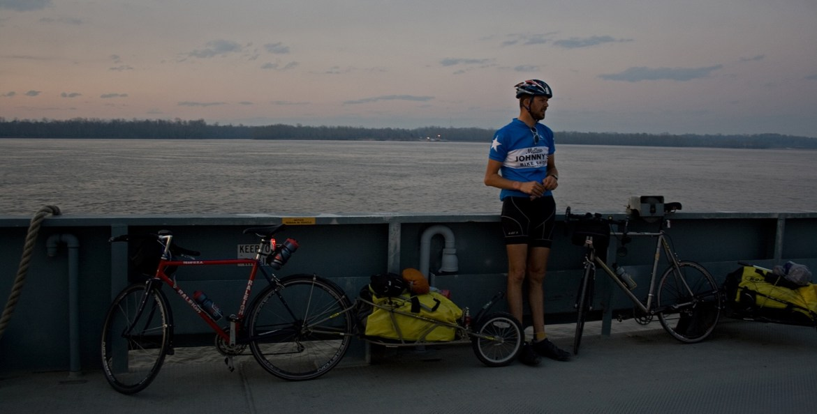 a touring cyclist rides a ferry across the Mississippi River in Louisiana