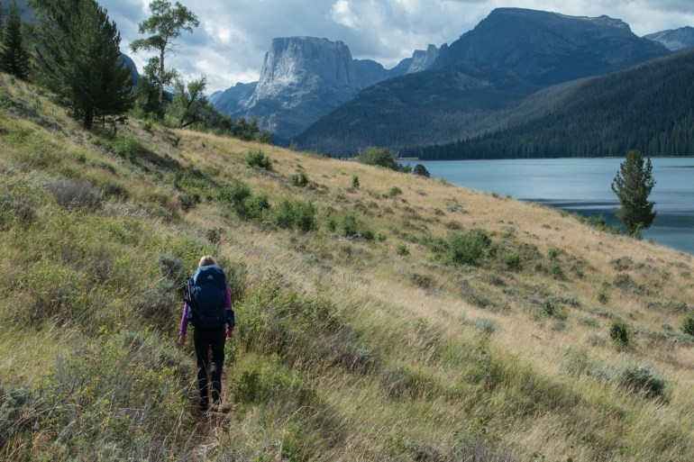 Hilary Oliver hikes past Green River Lake with Squaretop Mountain in the background in Wyoming's Wind River Range