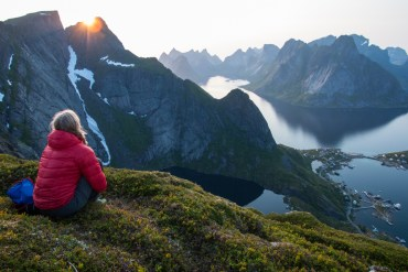 Hilary Oliver looks out over the fjords and peaks near Reine, Norway, from the top of the Reinebringen.