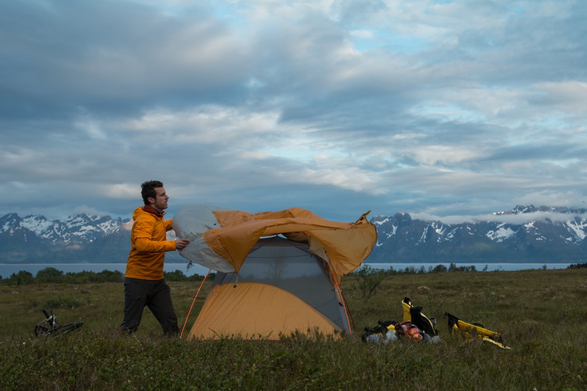 Brendan Leonard throws on the tent fly to set up camp within view of a fjord and mountain range during a bike tour of the islands of northern Norway.