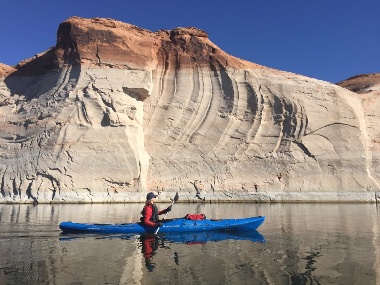 a kayak in front of one of the walls of glen canyon