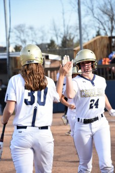 Maddie Vasquez congratulates her teammate Sydney Hines on a hit
