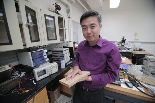 Associate Professor Xudong Wang holds a prototype of the researchers' energy harvesting technology, which uses wood pulp and harnesses nanofibers. The technology could be incorporated into flooring and convert footsteps on the flooring into usable electricity. (Source: Stephanie Precourt/UW-Madison)
