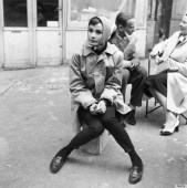 Actress Audrey Hepburn (1929 - 1993) sitting on a crate near the Eiffel Tower in Paris, during the filming of 'Funny Face', 1956. Co-star Fred Astaire (1899 - 1987) is behind her. (Photo by Paramount Pictures/Getty Images)