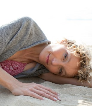 Portrait of a senior beautiful woman laying down on a sandy beach shore, looking and smiling at camera on holiday, nature outdoors. Travel lifestyle and healthy living, sunny exterior.