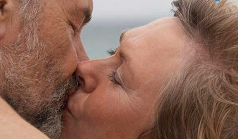 older man and woman kissing