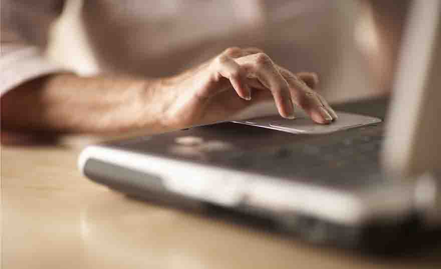Senior woman using laptop, close-up of hand on touchpad