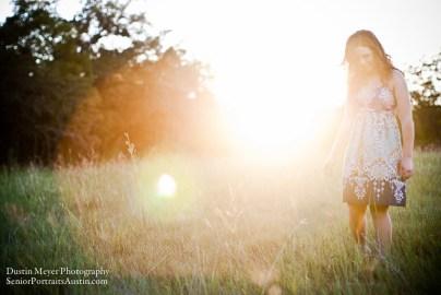Brunette teen female model sun flare backlit purple print hippie dress grass field sunset photo