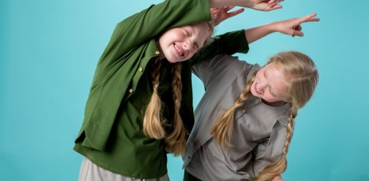 Two girls with long blonde plaits playing together