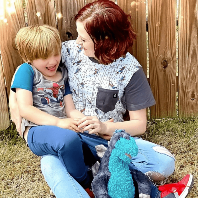 A photo of Alicia and her son. They are both wearing short-sleeved shirts and Alicia is smiling at her son