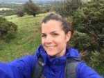 Helen Forester smiling at the camerawearing a blue jacket on a mountain with her hair in a bun
