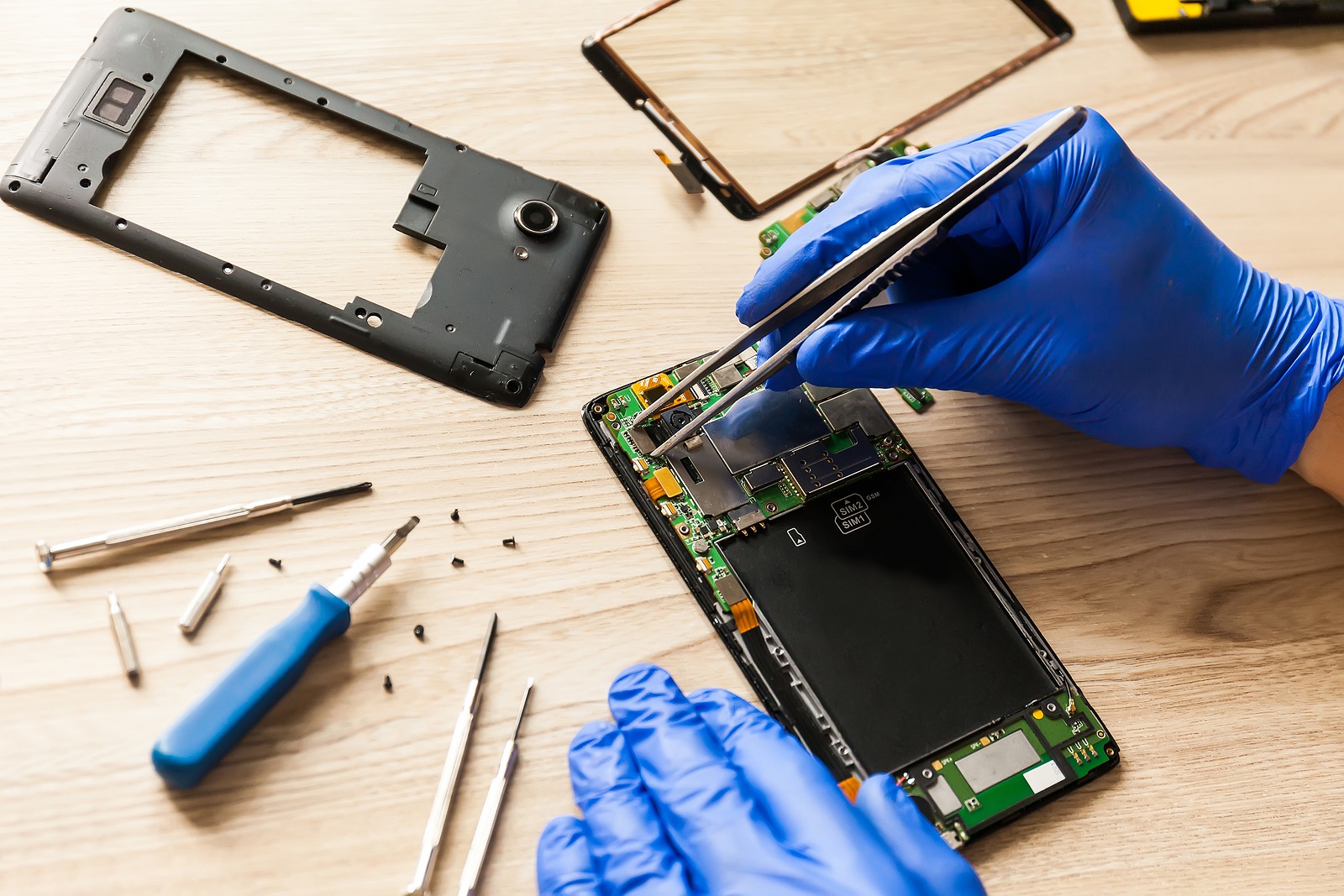 The technician repairing the smartphone's motherboard in the workshop on the table. Concept of computer hardware, mobile phone, electronic, repairing, upgrade and technology.