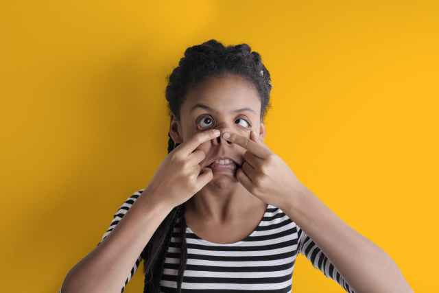 young funny african american woman grimacing in studio