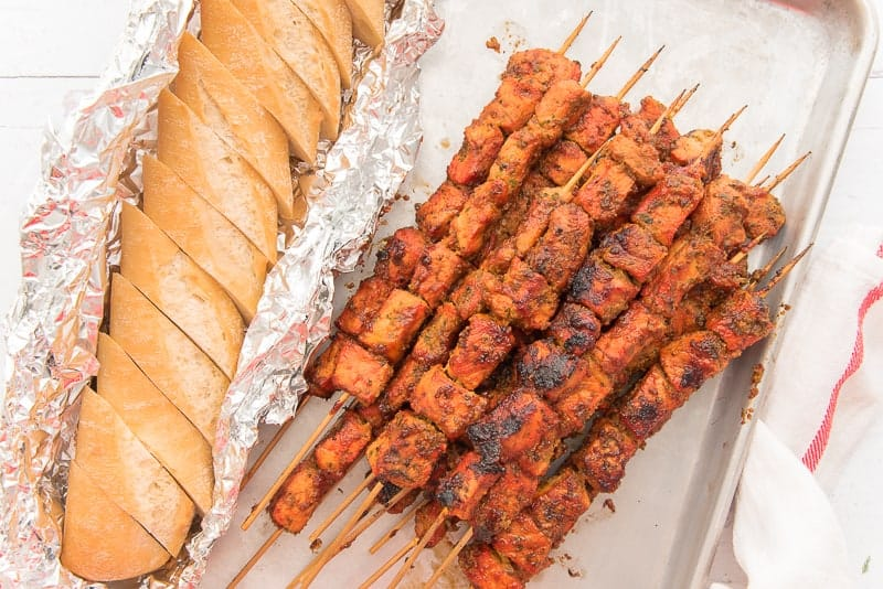 A close-up horizontal image of the Pinchos on a sheetpan next to a loaf of bread sliced in aluminum foil