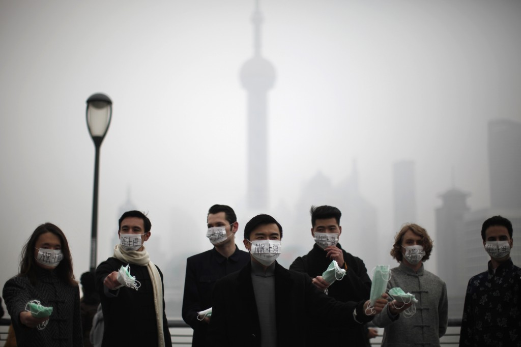 A group of expatriates stand along the Bund as they distribute face masks to pedestrians to raise awareness of air pollution in downtown Shanghai