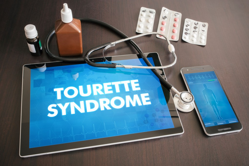 """Photo of a table containing a tablet, a mobile phone, a stethoscope, some pills and two bottles. On the tablet are the words """"Tourette Syndrome"""", while the mobile phone shows the outline of a person."""