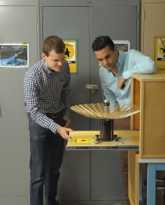 RainCube's radiofrequency lead Nacer Chahat (right) and mechanical engineer lead Jonathan Sauder (left) observe the CubeSat's deployed antenna. (Credit: NASA/JPL-Caltech)