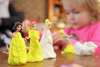 selective focus photography of three disney princesses figurines on brown surface