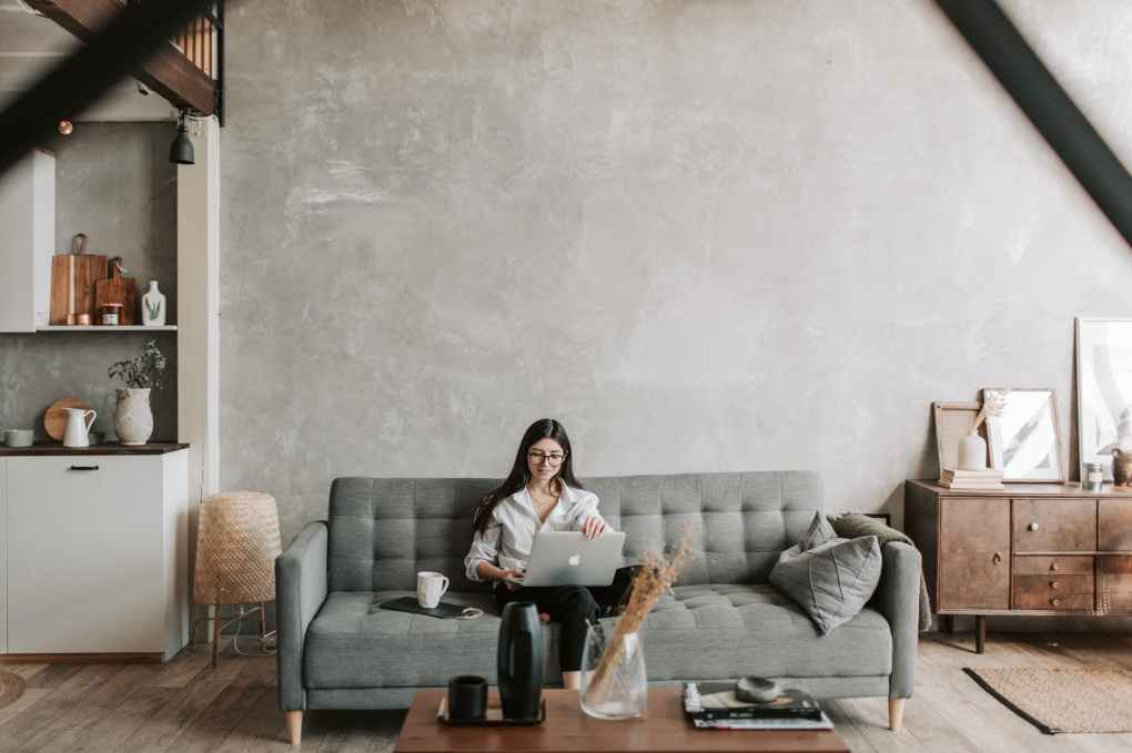 cheerful freelancer working on laptop in loft style apartment