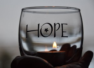 """the word """"Hope"""" above a candle"""