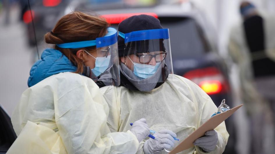 Deux travailleuses de la santé, portant un masque, une visière et des gants discutent d'un cas.
