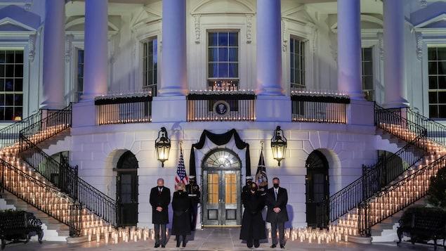 Joe et Jill Biden, ainsi que Kamala Harris et son conjoint, Doug Emhoff, la tête baissée, près des escaliers où sont disposés des centaines de chandelles allumées à l'extérieur de la Maison-Blanche.