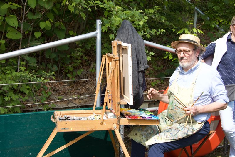 Un peintre avec ses pinceaux et sa toile regarde son motif, en l'occurence les danseurs