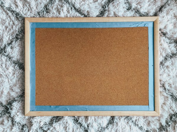 Cork Board with Edge Taped in Blue Painter's Tape for Easy Cork Board DIY