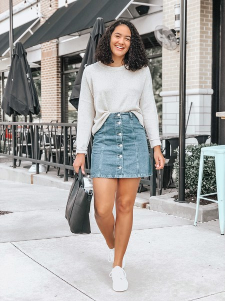 Girl with curly hair wearing a beige knit sweater, a denim mini skirt, white platform sneakers, a black tote bag all from H&M.