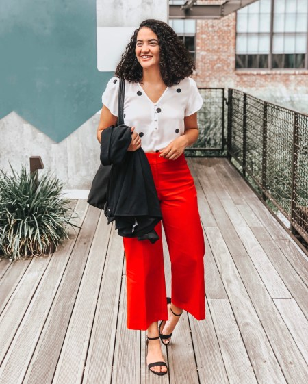 Girl with curly hair wearing a Polka Dot Petal Sleeve Blouse from LOFT, Red Wide Leg Riviera Pants from LOFT, Black Block Heels from Target, and a Black Knit Blazer from LOFT.