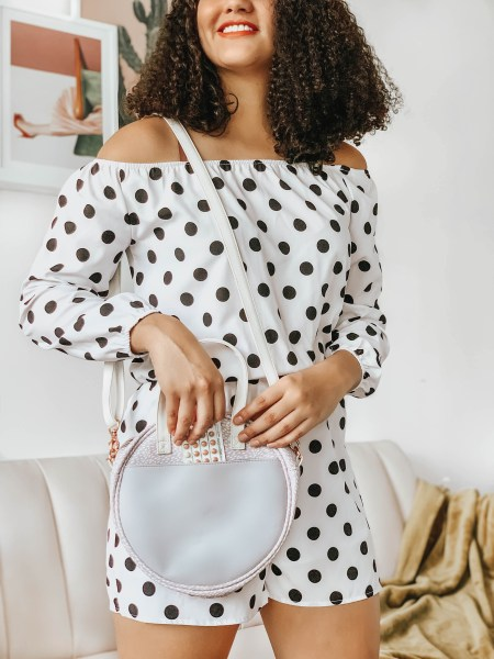 Girl with curly hair wearing a polka dot romper, a purple crossbody bag, and standing in front of a couch and wall hangings.