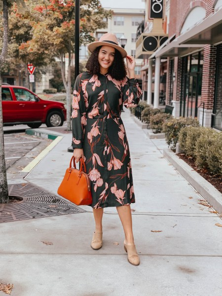 Girl with curly hair wearing a floral dress from Target, tan booties, an orange tote bag, and a tan hat.