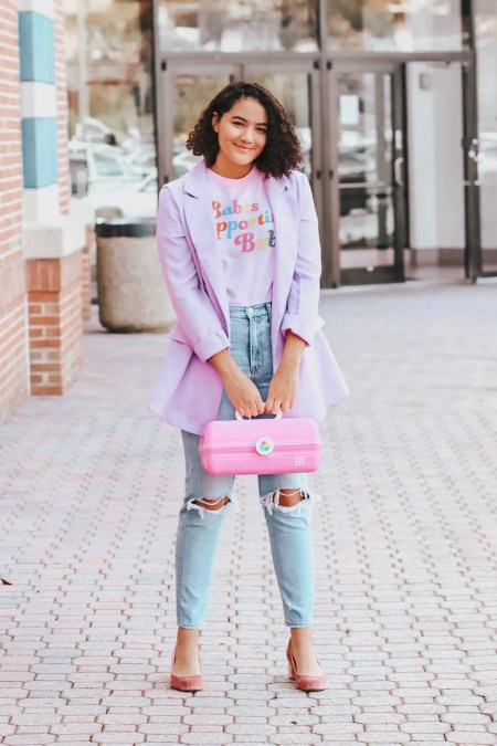 "Girl with curly hair wearing a purple blazer, a graphic tee that says ""babes supporting babes,"" busted knee mom jeans, pink velvet block heels, and carrying a caboodle."