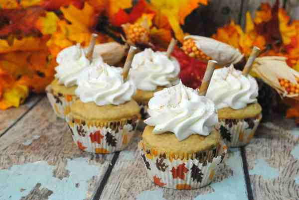 pumpkin spice latte cupcakes on a wood table with fake leaves in the background