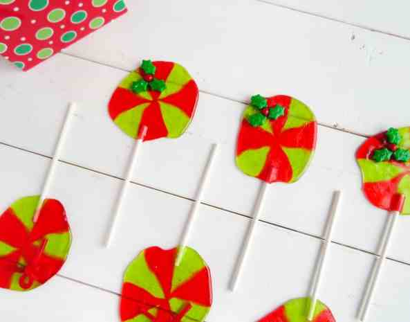 red and green jolly rancher suckers with a candy holly leaf at the top on a white table