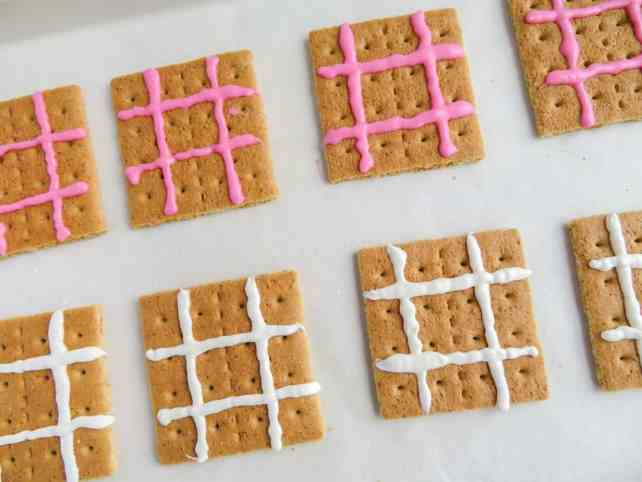graham crackers with pink or white icing lines on them to look like a tic tac toe board on a white background