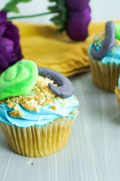 three moana cupcakes on a grey background with yellow linen and purple flower in the background