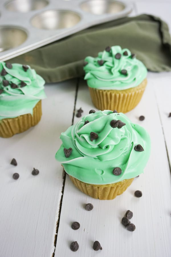three boozy andes mint cupcakes with chocolate chips and green linen in the background on a white table