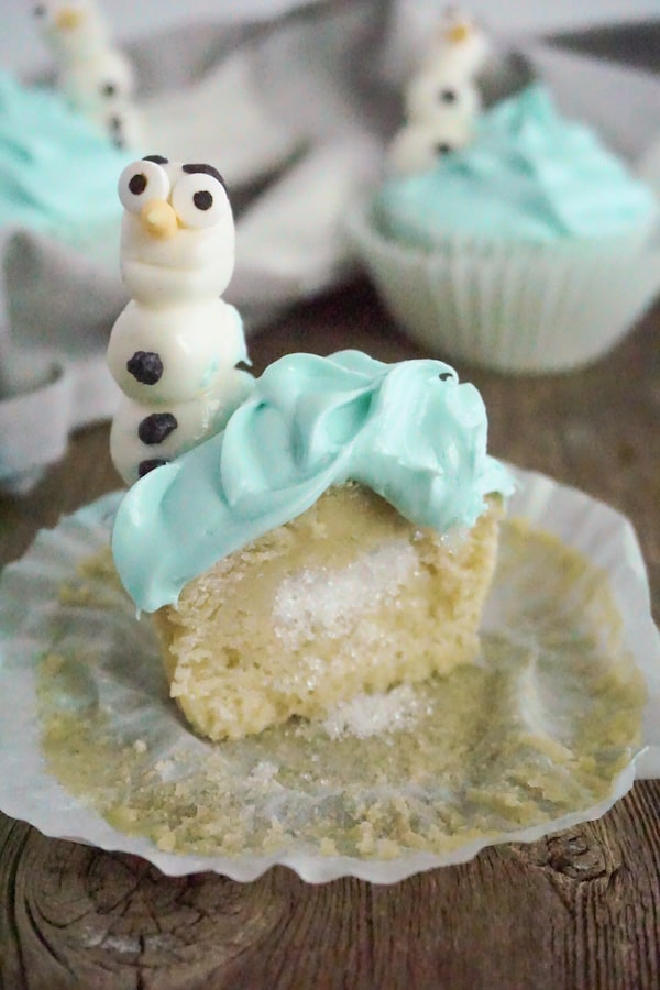 a cupcake cut open showing sprinkles hidden inside with Olaf character cupcake toppers on a wood table with a grey and white linen in the background