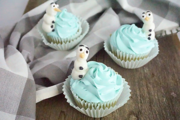 three cupcakes decorated with blue icing and a snowman resembling DIsney's Frozen Olaf character on top of the cupcake on a wood table with a grey and white linen in the background