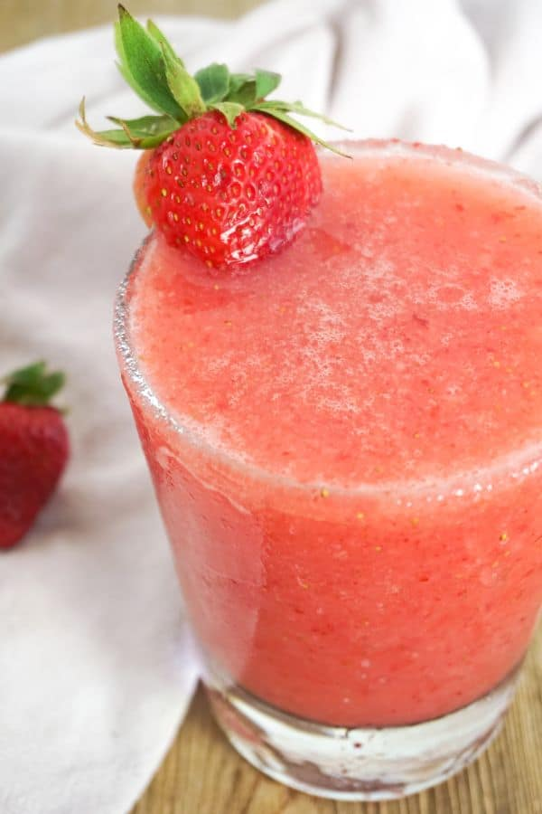 strawberry lemonade margarita in a glass with a strawberry on the side of the glass with another strawberry and white cloth in the background on a wood table