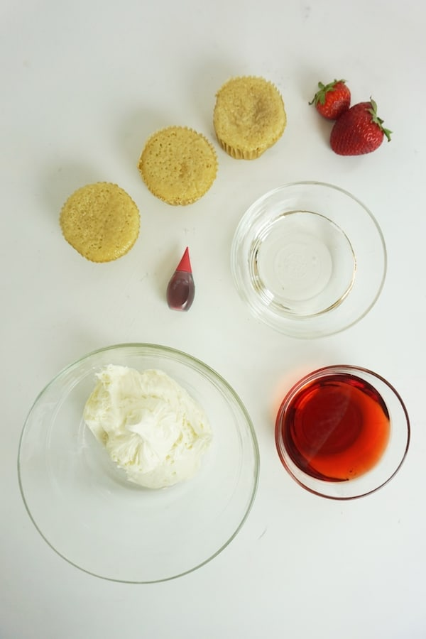ingredients for boozy strawberry cupcakes on a white table