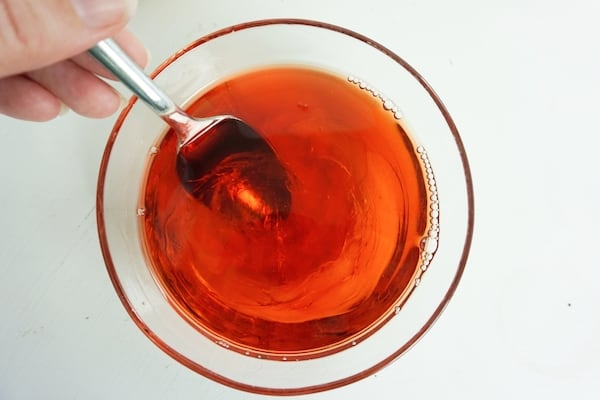 strawberry liqueur mixture in a bowl being stirred into corn syrup with a spoon on a white table