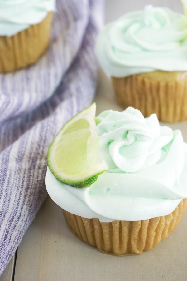 Tequila-Infused Margarita Cupcakes topped with green frosting and a slice of lime on a wood table next to a purple linen
